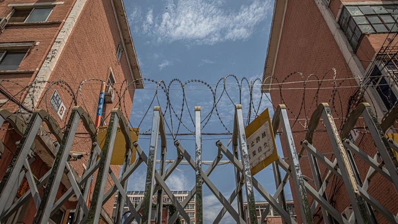 A barbed-wire fence stands at sealed off residential compound near the Yuquandong market, in Haidian district, Beijing, China. Source: AAP