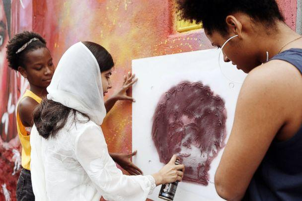 PHOTO: Malala Yousafzai does graffiti with girls from Rede Nami, a forum for young women to express themselves and speak out through street art. (Courtesy Luisa Dorr)