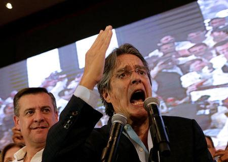 Ecuadorean presidential candidate Guillermo Lasso speaks near vice president candidate Andres Paez while waiting for the results of the national election in a hotel, in Guayaquil