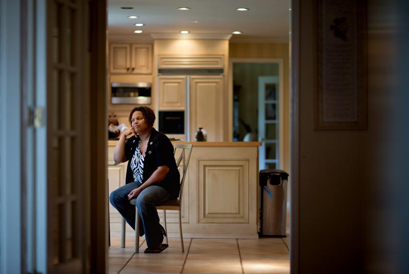 Yhonna Flowers sits in the home she shares with her four children and her mother, retired Atlanta police Det. Jaqueline Barber, Monday, Oct. 8, 2012, in Fayetteville, Ga. Less than a year after Occupy Atlanta members clashed with police in riot gear in a downtown park, they're now protesting alongside officers to help Barber avoid losing her home to foreclosure. Barber said she is under threat of eviction after her medical bills mounted, partly because of a diagnosis of multiple myeloma, a form of blood cell cancer. If she's evicted along with her daughter and four granchildren, she expects that she will be homeless. (AP Photo/David Goldman)