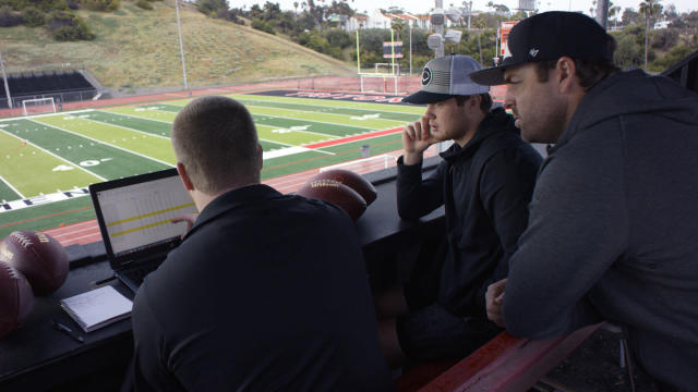 In this April 19, 2018, photo provided by Wilson Sporting Goods, Wilson Labs engineer Dan Hare, left, explains to quarterback Sam Darnold, center, and his mentor and former quarterback Jordan Palmer, right, data gathered from throwing a football using the Wilson Connected Football System, at San Clemente High School in San Clemente, Calif. Darnold and Palmer are serving as advisors for Wilson Sporting Goods, which makes the official balls used by the NFL. (Wilson Sporting Goods via AP)