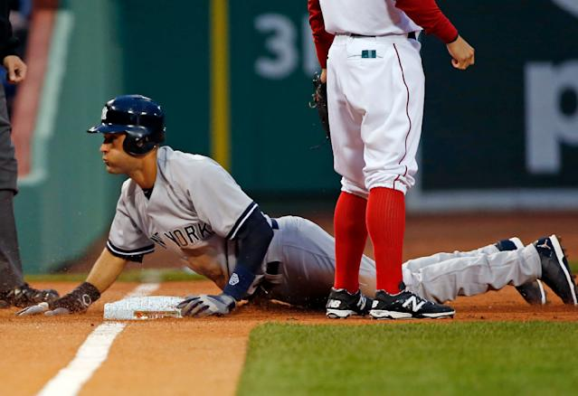 New York Yankees' Derek Jeter slides safely into third base on a passed ball and throwing error by Boston Red Sox catcher A.J. Pierzynski during the first inning of a baseball game at Fenway Park in Boston, Tuesday, April 22, 2014. (AP Photo/Elise Amendola)