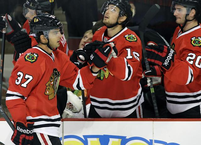 Chicago Blackhawks' Brandon Pirri (37) celebrates with teammates after scoring a goal during the first period of an NHL hockey game against the St. Louis Blues in Chicago, Thursday, Oct. 17, 2013. (AP Photo/Nam Y. Huh)
