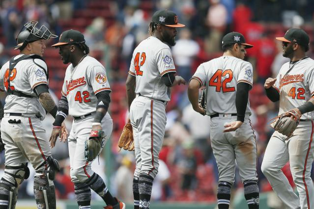 Baltimore Orioles' Miguel Castro, center, and Jesus Sucre, left, celebrate with teammates after defeating the Boston Red Sox during a baseball game in Boston, Monday, April 15, 2019. The players are all wearing (42) in honor of Jackie Robinson Day.(AP Photo/Michael Dwyer)