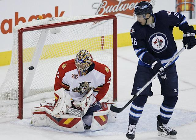 Winnipeg Jets' Blake Wheeler (26) deflects the shot for a goal against Florida Panthers goaltender Jacob Markstrom during the first period of an NHL hockey game in Winnipeg, Manitoba on Friday, Dec. 20, 2013. (AP Photo/The Canadian Press, John Woods)
