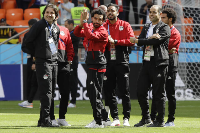 """Egypt's <a class=""""link rapid-noclick-resp"""" href=""""/soccer/players/380927/"""" data-ylk=""""slk:Mohamed Salah"""">Mohamed Salah</a>, center, waves to supporters as he arrives for the group A match between Egypt and Uruguay at the 2018 soccer World Cup in the Yekaterinburg Arena in Yekaterinburg, Russia, Friday, June 15, 2018. (AP Photo/Mark Baker)"""