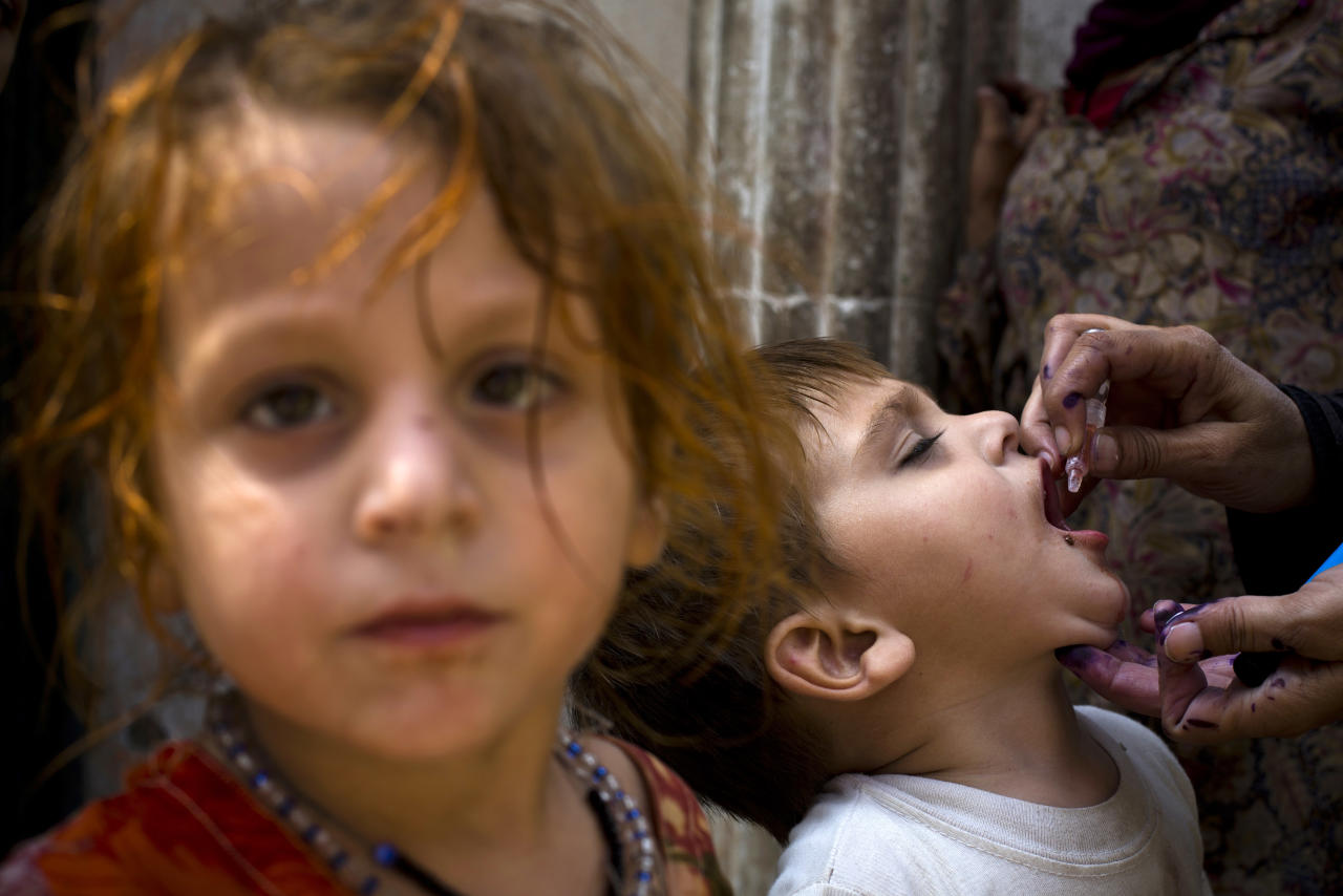 A Pakistani health worker gives a polio vaccine to a child in Rawalpindi, Pakistan, Monday, Oct. 7, 2013. A bomb exploded in Peshawar next to a van carrying Pakistani security guards tasked with protecting workers involved in an anti-polio drive in the country's northwest on Monday, killing two people, according to officials. (AP Photo/B.K. Bangash)
