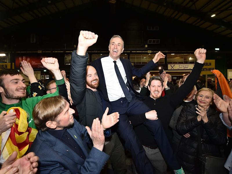 Newly elected Sinn Fein candidate Chris Andrews is held aloft by supporters: Getty