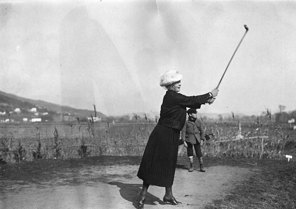 <p>A woman practices her swing on the golf course while a young boy watches on. </p>