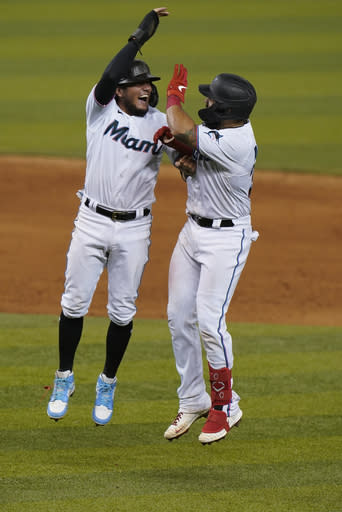 Miami Marlins' Miguel Rojas, left, celebrates with Jorge Alfaro after Alfaro hit a single scoring Monte Harrison to defeat the Philadelphia Phillies in the ninth inning of a baseball game, Thursday, Sept. 10, 2020, in Miami. (AP Photo/Wilfredo Lee)