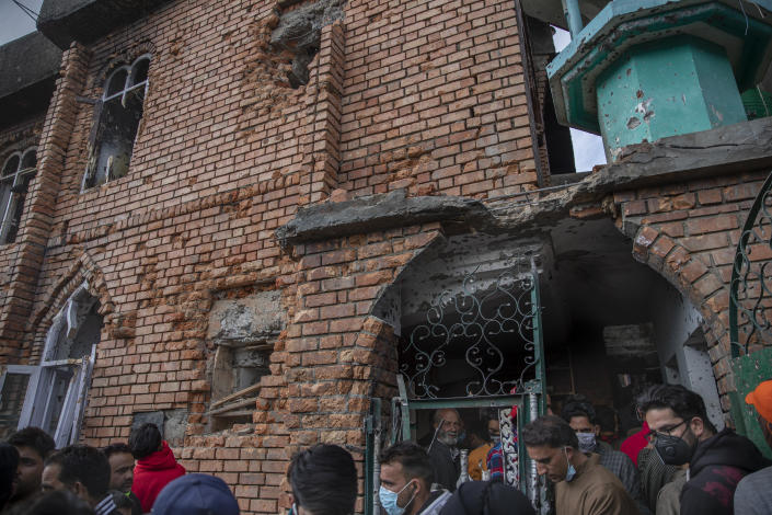 Kashmiri villagers inspect a mosque partially damaged during a gunbattle between Indian soldiers and suspected militants in Shopian, south of Srinagar, Indian controlled Kashmir, Friday, April 9, 2021. Seven suspected militants were killed and four soldiers wounded in two separate gunfights in Indian-controlled Kashmir, officials said Friday, triggering anti-India protests and clashes in the disputed region. (AP Photo/ Dar Yasin)