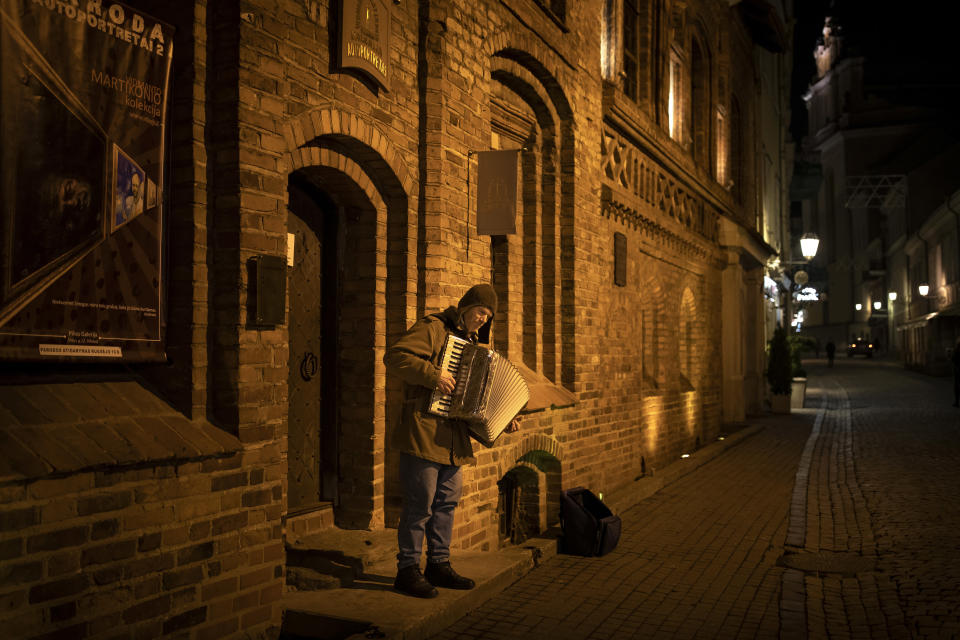 A street musician plays his accordion on a frosty spring evening in an empty Old Town in Vilnius, Lithuania, Tuesday, March 23, 2021. The quarantine restrictions have contributed to slowing the spread of the coronavirus (COVID-19) in Lithuania, but morbidity rates are still high. (AP Photo/Mindaugas Kulbis)