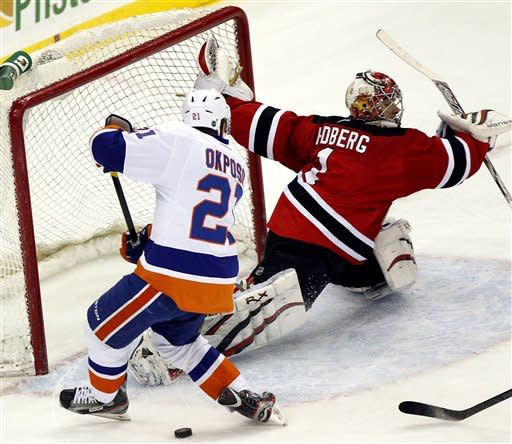 New Jersey Devils goalie Johan Hedberg (1), of Sweden, makes a save as New York Islanders' Kyle Okposo (21) tries to score in the third period of an NHL hockey game, Tuesday, April 3, 2012, in Newark, N.J. The Devils won 3-1. (AP Photo/Julio Cortez)