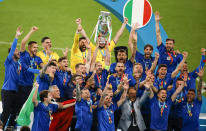 Italy celebrate with their trophy after defeating England in a penalty shootout at the Euro 2020 soccer championship final at Wembley stadium in London, Sunday, July 11, 2021. (John Sibley/Pool Photo via AP)