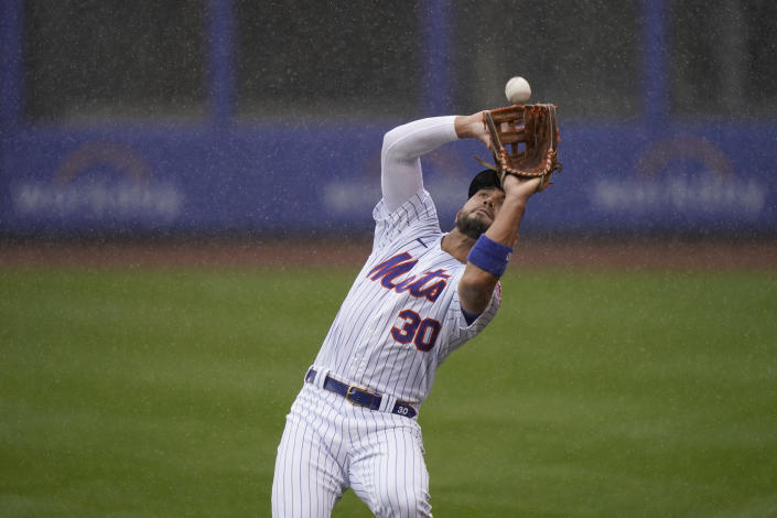 New York Mets right fielder Michael Conforto catches a fly ball in the rain during the first inning of a baseball game at Citi Field, Sunday, April 11, 2021, in New York. The game was delayed at the top of the first inning due to rain. (AP Photo/Seth Wenig)