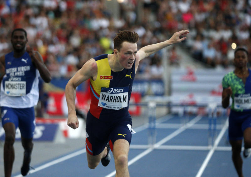 Karsten Warholm of Norway, center, competes on his way to win the men's 400m hurdles at the IAAF Diamond League athletics meeting at Charlety Stadium in Paris, Saturday, Aug. 24, 2019. (AP Photo/Michel Spingler)