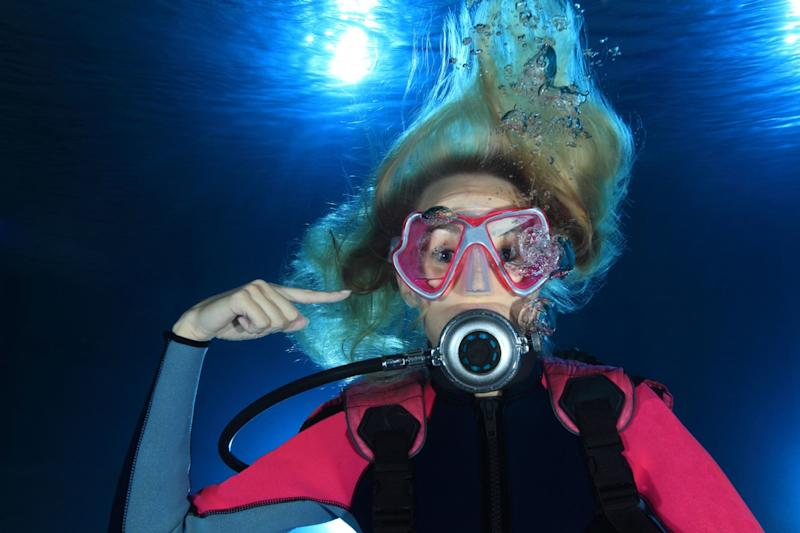 Female scuba diver show the underwater sign for ear problems