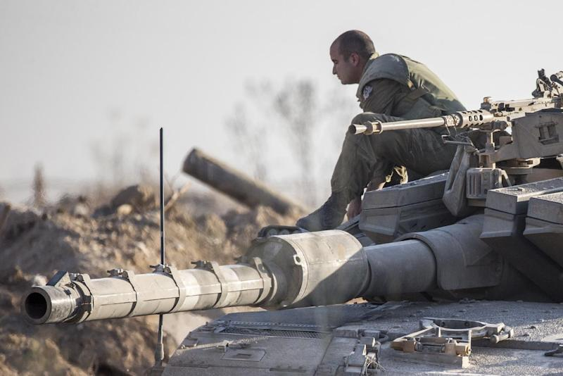 An Israeli soldier sits on a Merkava tank on July 17, 2014 at an army deployment area near Israel's border with the Gaza Strip