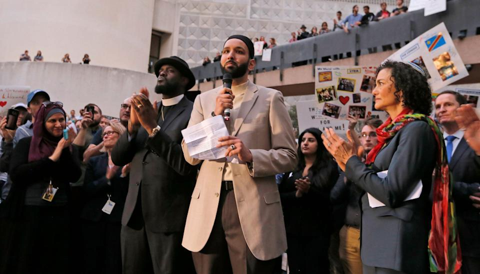 Imam Omar Suleiman speaks flanked by Dr. Michael W. Watson, left, and Rabbi Nancy Kasten, all from Faith Forward, at a vigil for refugees on Monday, Jan. 30, 2017 in Dallas, Texas at Thanksgiving Plaza.
