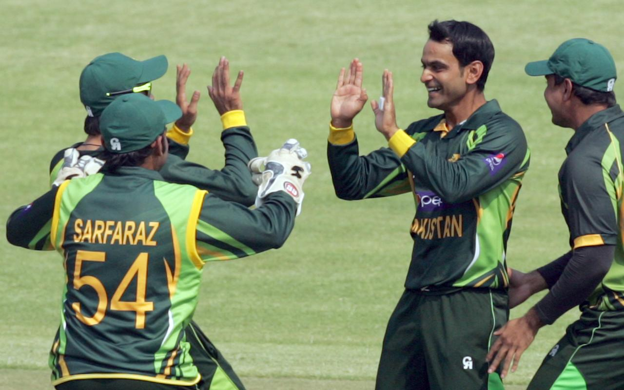 Pakistan bowler Muhammad Hafeez (2nd R) celebrates a wicket with teammates during the final game of the three match ODI cricket series between Pakistan and hosts Zimbabwe at the Harare Sports Club on August 31, 2013.  AFP PHOTO / JEKESAI NJIKIZANA        (Photo credit should read JEKESAI NJIKIZANA/AFP/Getty Images)
