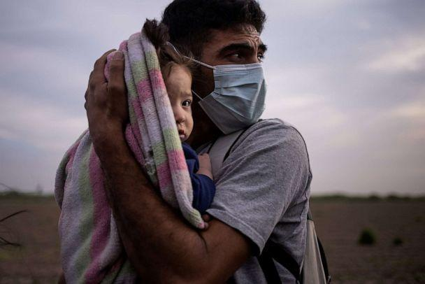 Francisco, 34, an asylum seeking migrant from Honduras, cradles his nine-month-old daughter Megan as they await for transport to a processing center after crossing the Rio Grande river into the US from Mexico on a raft in La Joya, Texas, March 25, 2021. (Adrees Latif/Reuters)