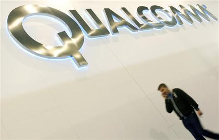 A man walks past a Qualcomm advertising logo at the Mobile World Congress at Barcelona, February 27, 2013. REUTERS/Albert Gea/Files