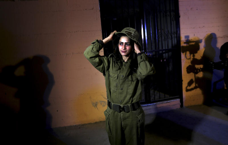 "In this Wednesday, Jan. 29, 2014 photo, Fayka al-Najar, who plays an Israeli female soldier, adjusts her hat on the set of a movie being made in Gaza called, '' Losing Shalit,'' adjusts her hat during filming in Gaza City. ""Losing Schalit,"" currently being filmed in the blockaded territory, is the first of a planned three-part series about the 2006 capture of Israeli soldier Gilad Schalit by gunmen allied with the Islamic militant Hamas movement. Parts two and three will depict Schalit's time in captivity and his 2011 swap for hundreds of Palestinian prisoners held by Israel. (AP Photo/Hatem Moussa)"