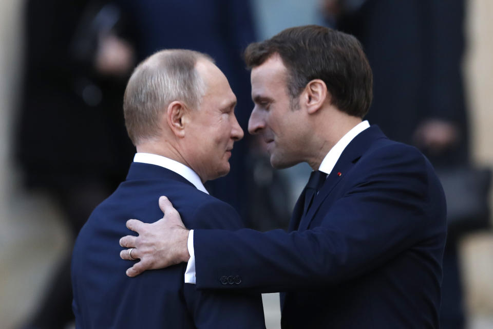 French President Emmanuel Macron, right, welcomes Russian President Vladimir Putin wave at the Elysee Palace Monday, Dec. 9, 2019 in Paris. A long-awaited summit in Paris is aiming to find a way to end the war in Ukraine, after five years and 14,000 lives lost in a conflict that has emboldened the Kremlin and reshaped European geopolitics. (AP Photo/Thibault Camus)