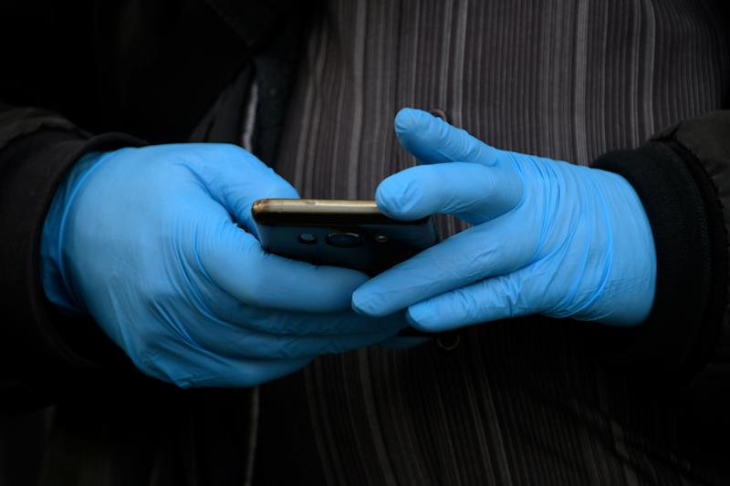 A person wearing gloves and using their mobile phone.