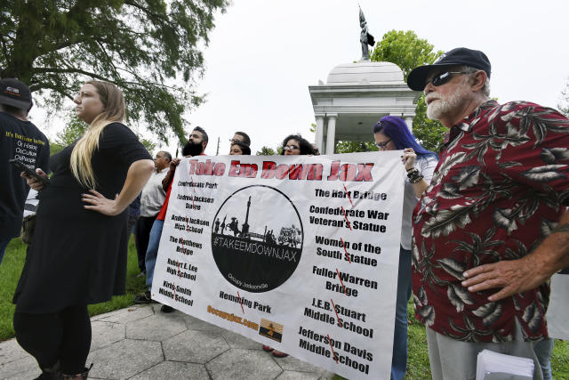 <p>Members of the Take Em Down Jax organization hold a banner with the list of offending confederate monuments as well as buildings and locations they want renamed during a rally in Jacksonville's Confederate Park in Jacksonville, Fla., Aug 15, 2017. Several organizations wanting the removal of confederate monuments and have the names changed on schools and bridges met at the base of the Woman of the Southland statue in Confederate Park North of downtown Jacksonville. Roughly 30 demonstrators against the monuments and around 10 who wanted them left alone were kept in check with the presence of around a dozen members of the Jacksonville Sheriffs Office. (Photo: Bob Self/The Florida Times-Union via AP) </p>