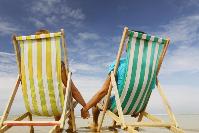 Man and woman on beach in deckchairs