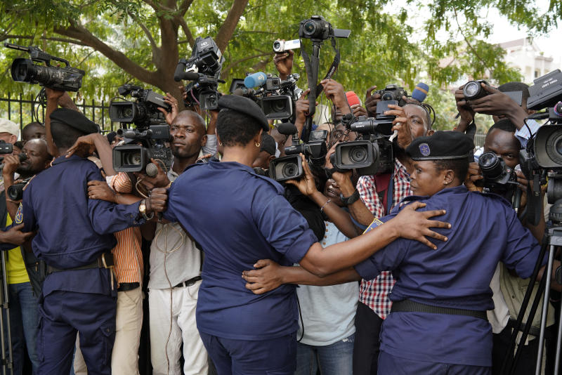 Congolese police officers hold back members of the media as Congo opposition candidate Martin Fayulu leaves the constitution court in Kinshasa, Congo, Saturday Jan. 12, 2019. The ruling coalition of Congo's outgoing President Joseph Kabila has won a large majority of national assembly seats, the electoral commission announced Saturday, while the presidential election runner-up was poised to file a court challenge alleging fraud. (AP Photo/Jerome Delay)