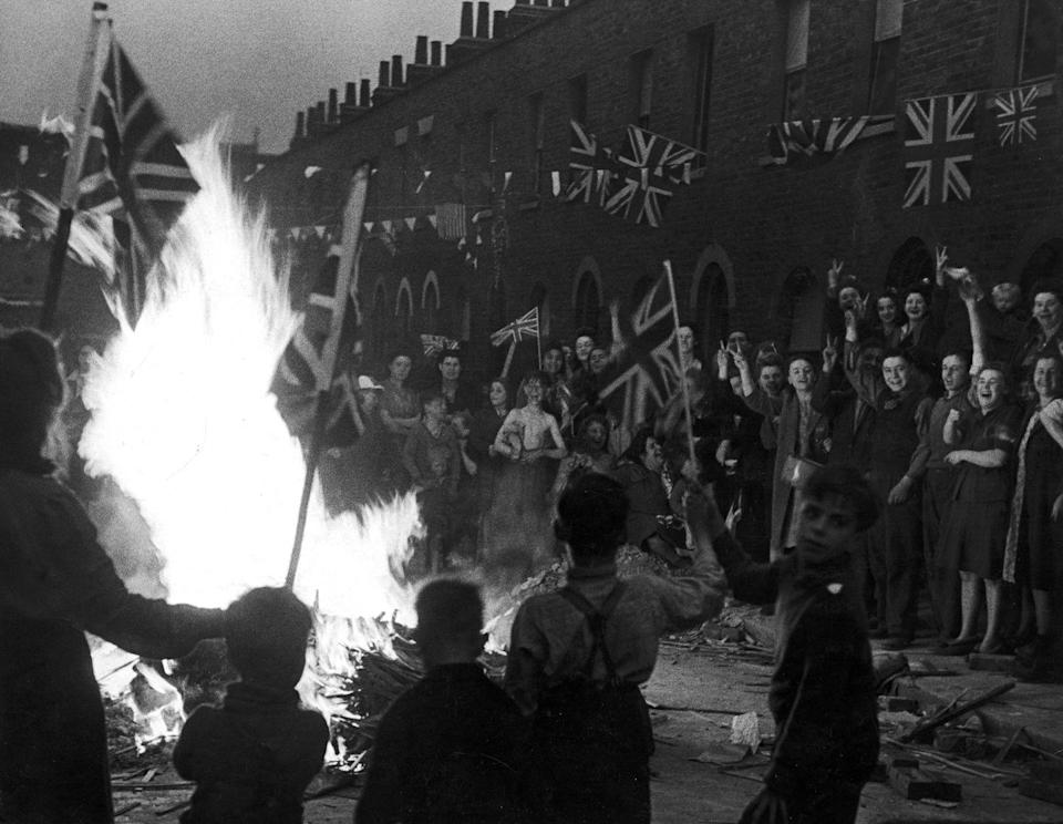 <p>In the streets of London, a crowd of joyous Brits wave flags around a bonfire built of material from bomb-wrecked homes.</p>