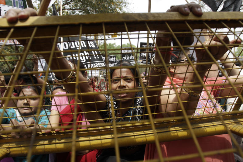 Women activists of India's main opposition Bharatiya Janata Party try to climb a police barricade near the residence of ruling Congress party president Sonia Gandhi during a protest against the rape of a 5-year-old girl in New Delhi, India, Sunday, April 21, 2013. The girl was allegedly kidnapped, raped and tortured by a man and then left alone for two days in a locked room in India's capital. (AP Photo/Tsering Topgyal)