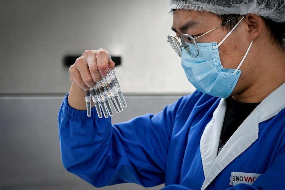 FILE PHOTO: A staff member checks vaccines during a media tour of a new factory built to produce a COVID-19 vaccine at Sinovac, one of 11 Chinese companies approved to carry out clinical trials of potential coronavirus vaccines, in Beijing on September 24, 2020. (Photo: WANG ZHAO/AFP via Getty Images)