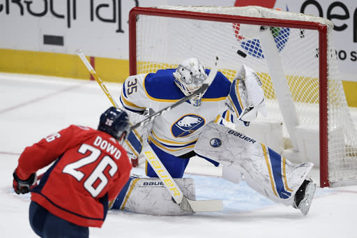 Washington Capitals center Nic Dowd (26) shoots the puck that went over the net against Buffalo Sabres goaltender Linus Ullmark (35) during the second period of an NHL hockey game, Sunday, Jan. 24, 2021, in Washington. (AP Photo/Nick Wass)
