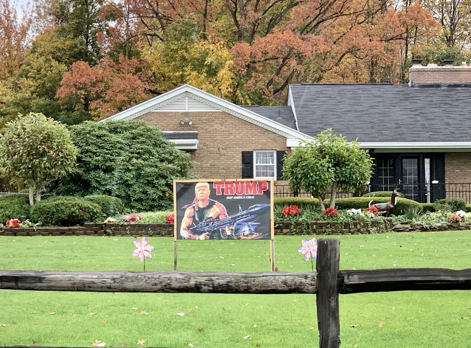 A lawn sign depicts President Trump as Rambo, armed with heavy weapons