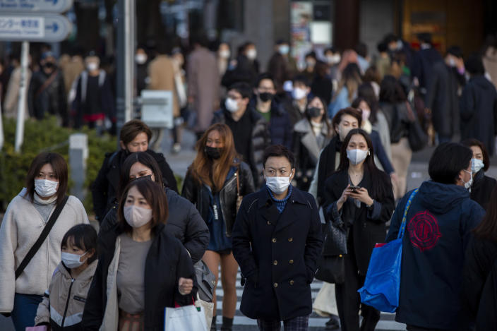 People wearing protective masks to help curb the spread of the coronavirus walk along a pedestrian crossing Sunday, Feb. 28, 2021, in Tokyo. Japan's second state of emergency set up to curb the coronavirus in Japan has been lifted in six urban areas this weekend and remain in the Tokyo area for another week until March 7. (AP Photo/Kiichiro Sato)