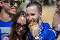 Artem Dolgopyat, Israeli artistic gymnastics men's gold medalist of Tokyo 2020, stands with his partner Maria Masha Sakovichas, while holding his medal on his arrival to Ben Gurion Airport, near Tel Aviv, Israel, Tuesday Aug. 3, 2021. The Ukrainian-born Israeli gymnast was hailed as a national hero for winning Israel's second-ever gold medal — and its first in artistic gymnastics. But the celebrations were tempered after his mother lamented that the country's authorities will not allow him to wed because he is not considered Jewish according to Orthodox law. (AP Photo/Ariel Schalit)