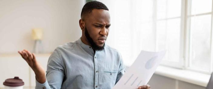 Paper Problems. Shocked African Businessman Looking Through Negative Financial Report And Tax Bills Working Sitting In Office. Bank Financial Issues Concept. Selective Focus