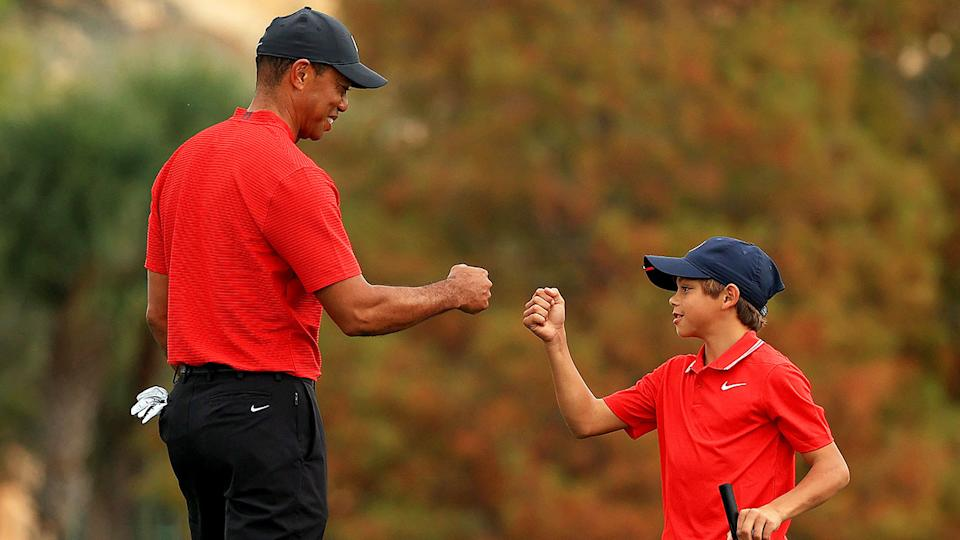 Seen here, Tiger Woods and son Charlie give one another a fist bump on the course.