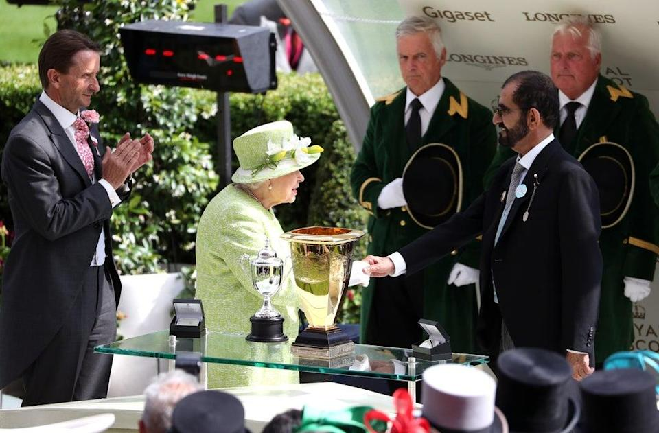 The Queen presents Godolphin founder Sheikh Mohammed bin Rashid Al Maktoum with a trophy during day five of Royal Ascot at Ascot Racecourse (Jonathan Brady/PA) (PA Archive)
