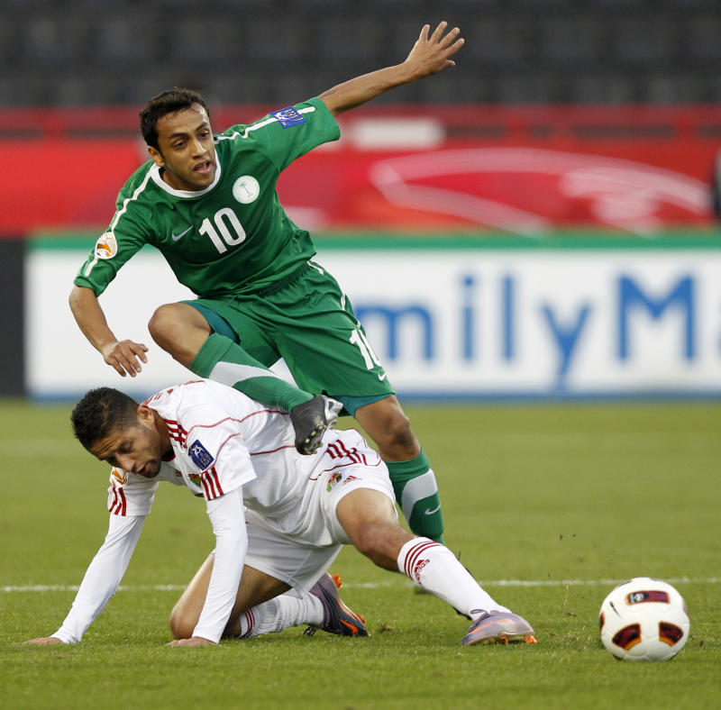 Jordan's player Hasan Abdel Fattah, bottom, fights for the ball with Saudi Arabia's player Mohammed Al Shalhoub during their AFC Asian Cup group B soccer match at Al Rayyan Stadium, in Doha, Qatar, Thursday, Jan. 13, 2011. (AP Photo/Kin Cheung)