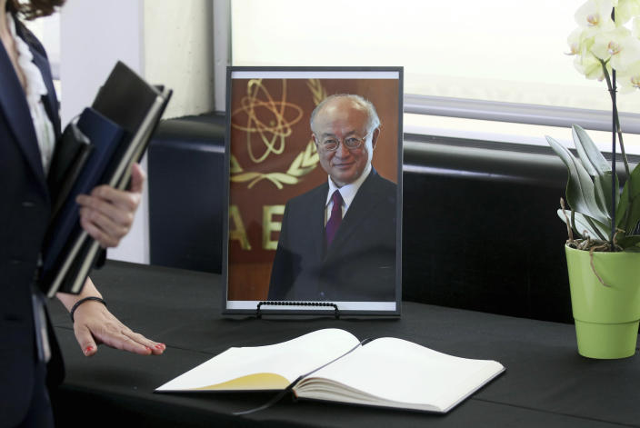 A book of condolence in front of a portrait photo of the Director General of the International Atomic Energy Agency, IAEA, Yukiya Amano from Japan is positioned in Vienna, Austria, Monday, July 22, 2019. The IAEA announced the death of the agency's Director General Yukiya Amano at the age of 72 years. (AP Photo/Ronald Zak)