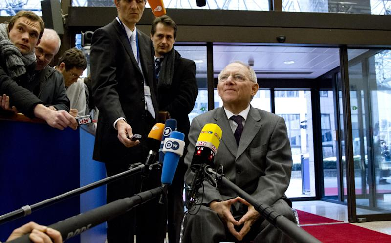 German Finance Minister Wolfgang Schaeuble, center, speaks with the media as he arrives for an extraordinary meeting of the eurogroup at EU headquarters in Brussels on Friday, March 15, 2013. European finance ministers are trying to complete a long-delayed bailout deal for Cyprus in a bid to keep the island nation from a bankruptcy that could rekindle the region's debt crisis. (AP Photo/Virginia Mayo)