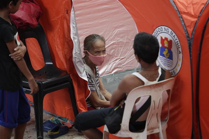 Residents take advantage of tents provided at an evacuation center as rains from a typhoon locally known as Goni start to pour in Manila, Philippines on Sunday, Nov. 1, 2020. A super typhoon slammed into the eastern Philippines with ferocious winds early Sunday and about a million people have been evacuated in its projected path, including in the capital where the main international airport was ordered closed. (AP Photo/Aaron Favila)