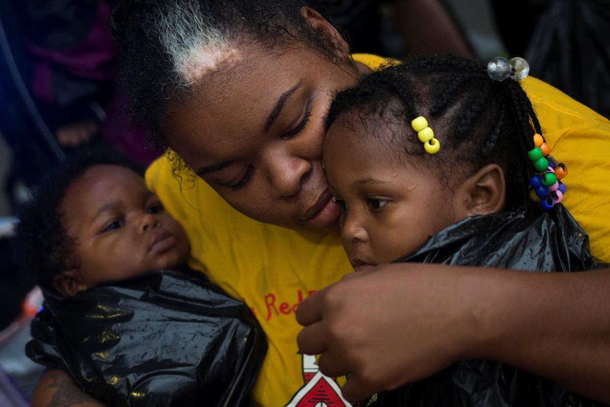 Laquanta Edwards holds her 1-year-old daughter Ladaja, right, and 9-month-old son LaDarius after they arrived to high ground by boat in east Houston.