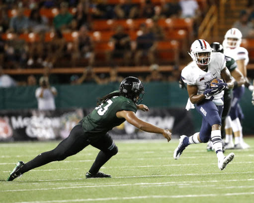 Hawaii linebacker Penei Pavihi (33) tries to catch Duquesne wide receiver Kellon Taylor (5) during the third quarter of an NCAA college football game Saturday, Sept. 22, 2018, in Honolulu. (AP Photo/Marco Garcia)