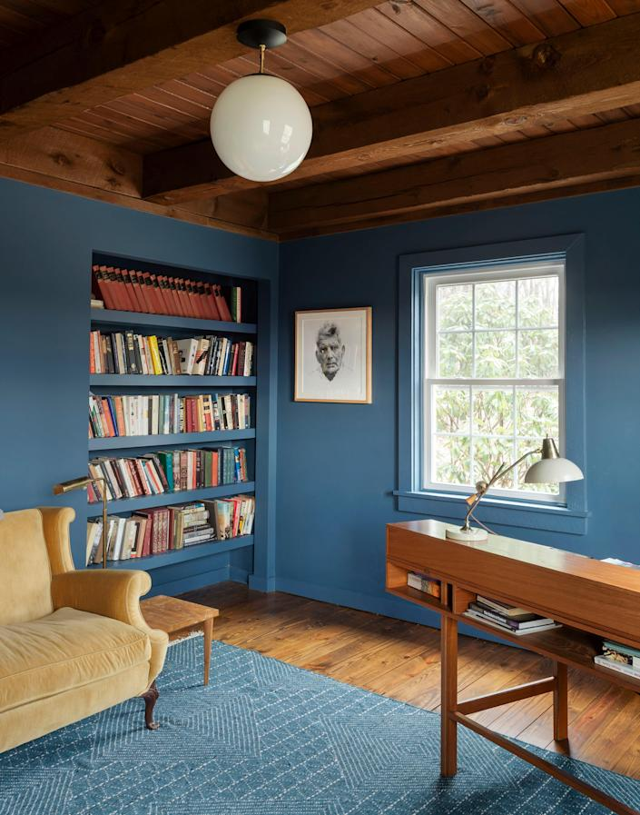 AFTER: The palette of the study features contrasting natural woods and blue hues. The walls are painted with Benjamin Moore Van Deusen Blue. The study has a built-in bookcase, vintage furniture, and a Cedar & Moss pendant light.