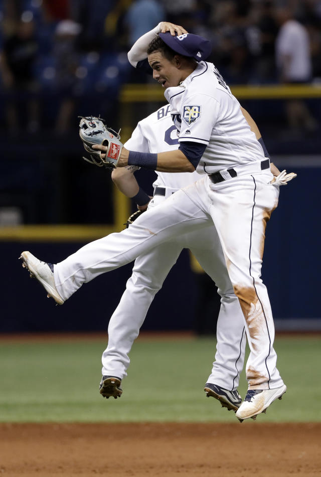 Tampa Bay Rays shortstop Willy Adames, front, and first baseman Jake Bauers (9) celebrate after they defeated the New York Yankees in a baseball game Friday, June 22, 2018, in St. Petersburg, Fla. (AP Photo/Chris O'Meara)